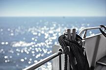 Detail Schiff mit glitzerndem Meer im Hintergrund