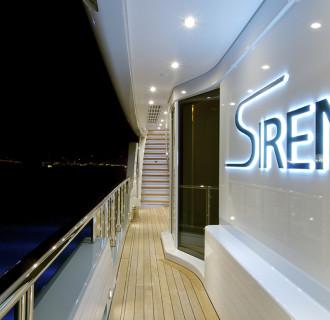 Luxusyacht Siren Außenaufnahme mit beleuchtetem Logo bei Nacht